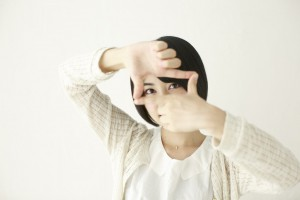 指で額縁を作る女性